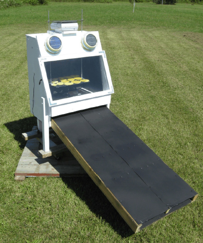 A small prototype solar dryer being used for research purposes. The large flat black surface is the heat collector.